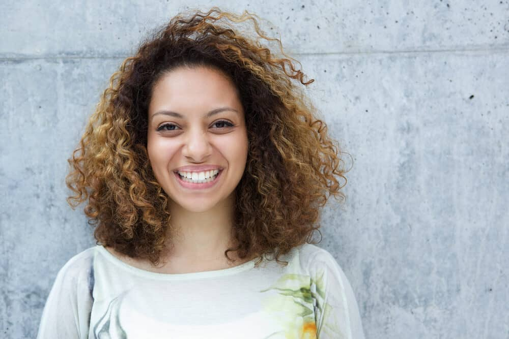 Black girl with natural curls leaning up against a gray wall wearing a green dress shirt with a flower on the left shoulder