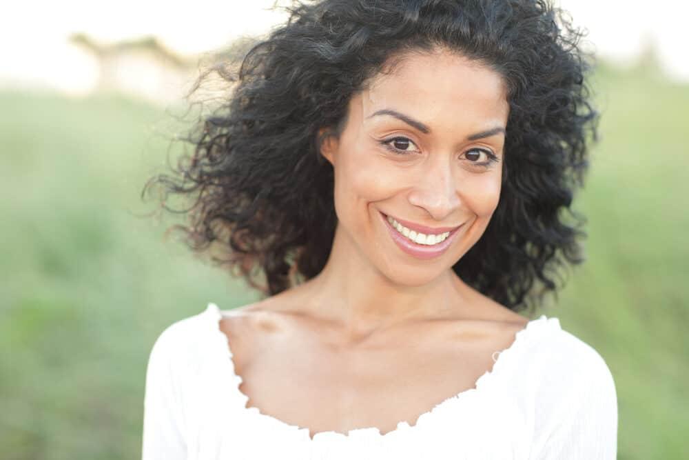 Cute African American women with long wavy hair wearing a white shirt