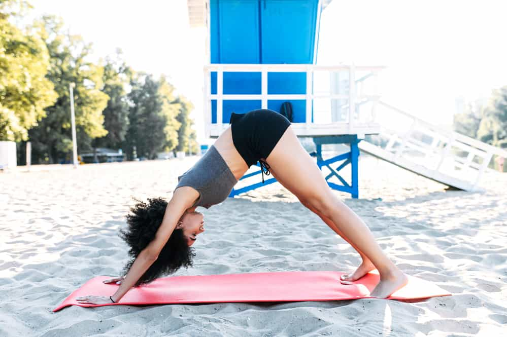 A mixed-race girl with natural hair is practicing yoga on a sandy beach on a sunny morning.