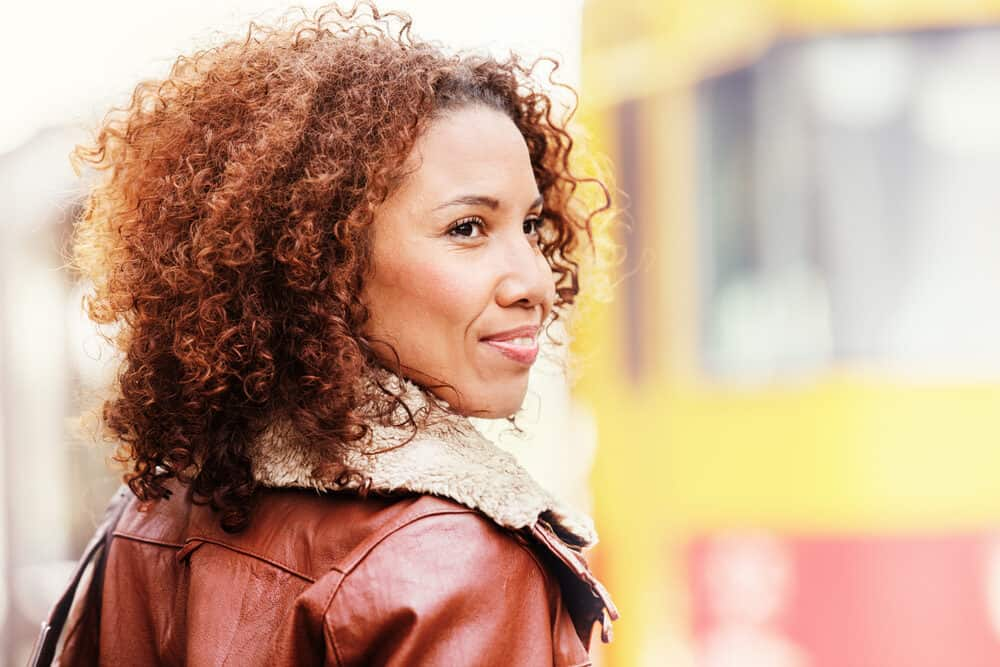 Black girl with hair bleached red and brown while wearing a red and brown jacket.
