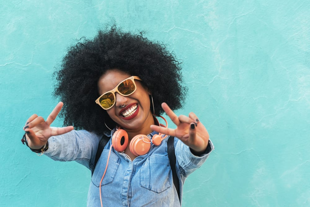 African-American girl with natural hair wearing a white t-shirt, blue jeans, and three necklaces.