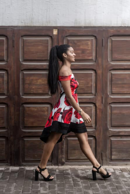 Black female walking home wearing high heels and ponytail weave on the back of her head.
