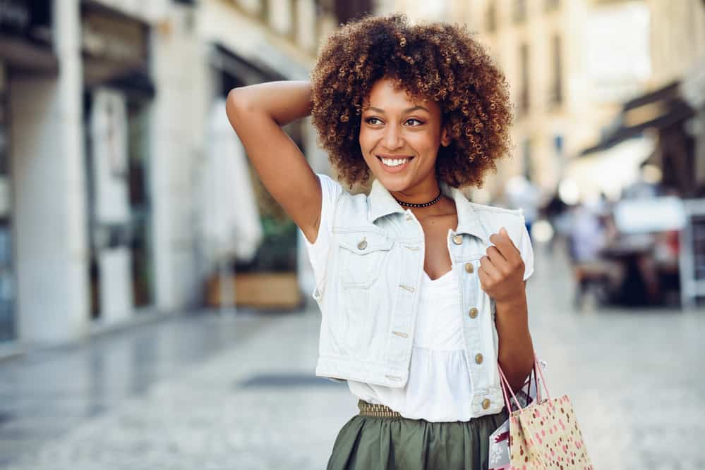African American female shopping at an outdoor mall coily coarse hair strands dyed brown by a celebrity hairstylist.