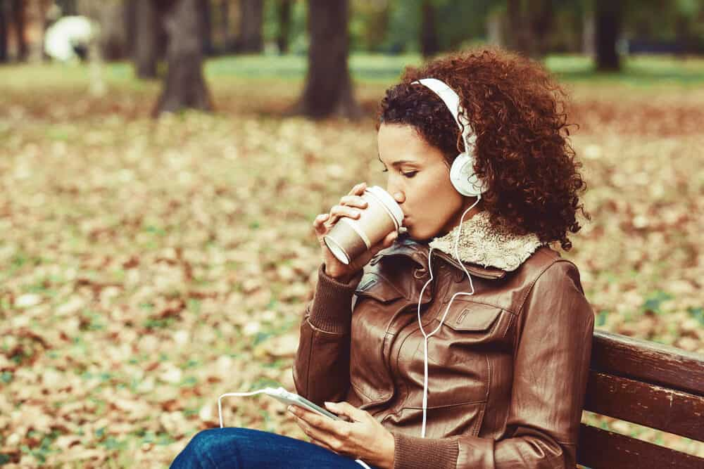 Women with 3c natural hair sitting in the park wearing a brown leather coat and drinking coffee.