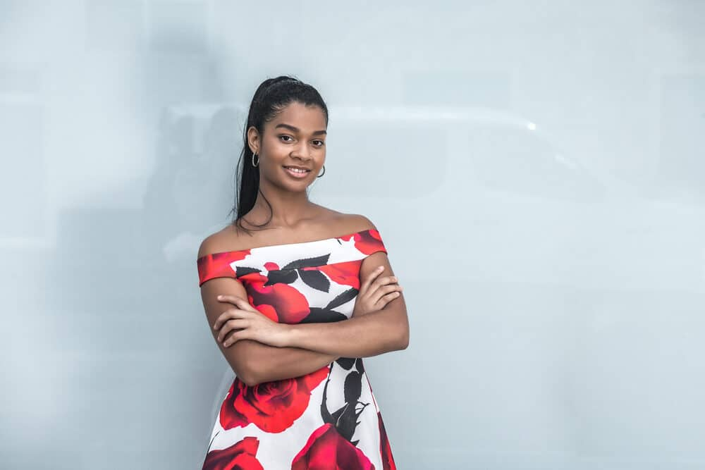 Black lady ready for the cover of Beauty News posing for a photo indoors with her arms folded wearing a colorful dress and a long ponytail on straightened hair.