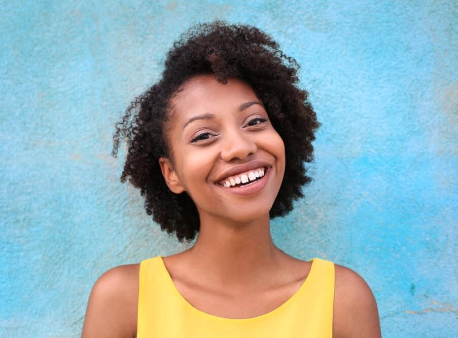 Cute black girl with curly precious hair wearing a yellow t-shirt.