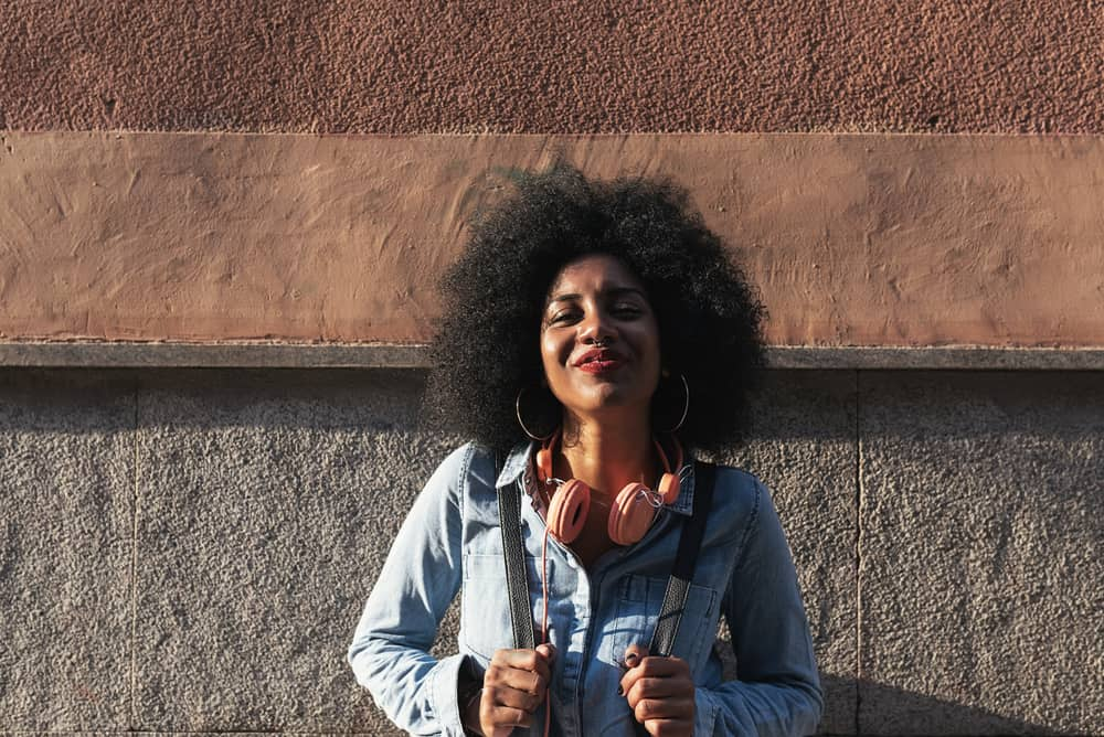 Black girl standing outside laughing while wearing a blue jean shirt and peach headphones.