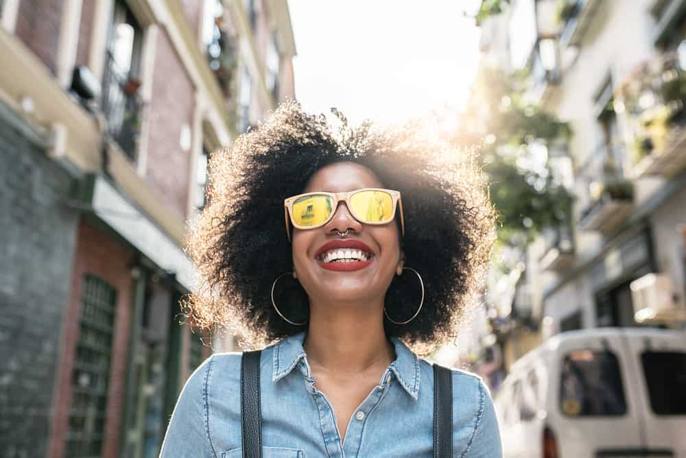 African American female with a natural hairstyle wearing a blue jean shirt, peach sunglasses, and red lipstick.