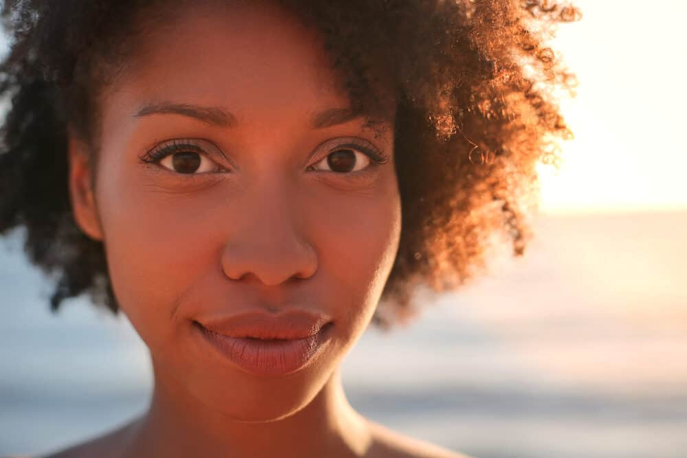Close-up of black women trying to avoid dry and damaged hair standing outside on a sunny day.