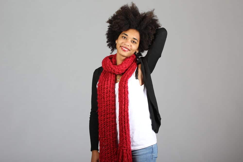 A woman with natural hair in an afro hairstyle wearing casual clothes.
