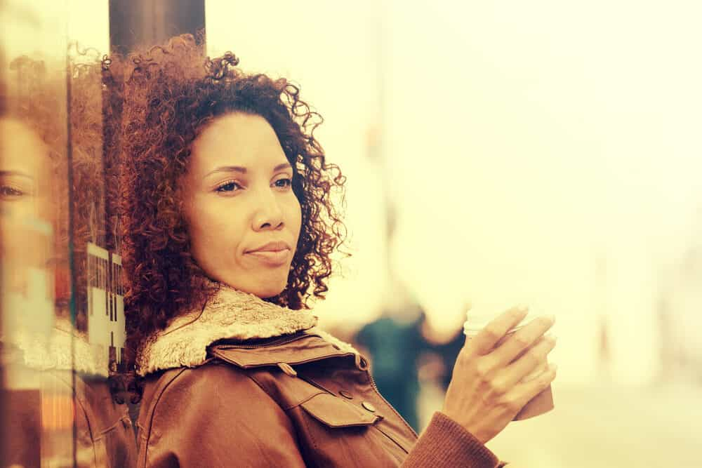 Black girl with naturally curly hair wearing a brown coat and drinking tea.