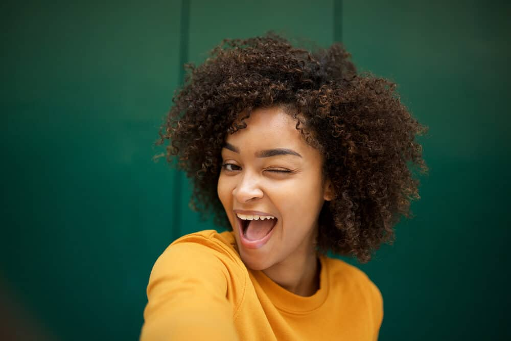 Black girl winking her left eye with a hair grease mix in her naturally curly hair strands.