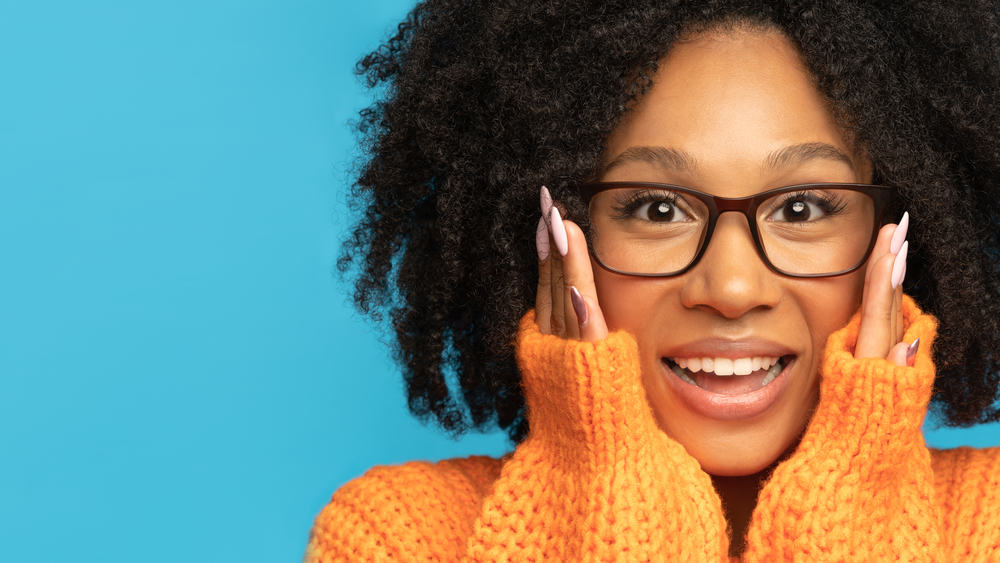 Excited black girl with curly hair wearing an orange sweater and peach fingernail polish.
