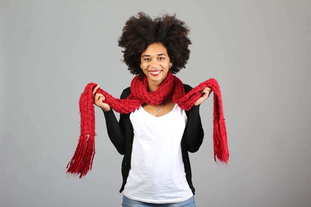 African American female wearing black pearl earrings, a silver necklace, red scarf, white t-shirt, and a black sweater.