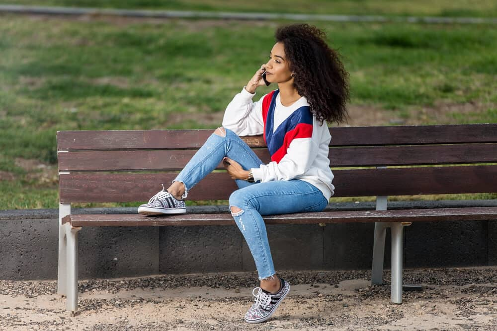African lady with virgin hair wearing curly weave while sitting on a park bench talking on a mobile phone.