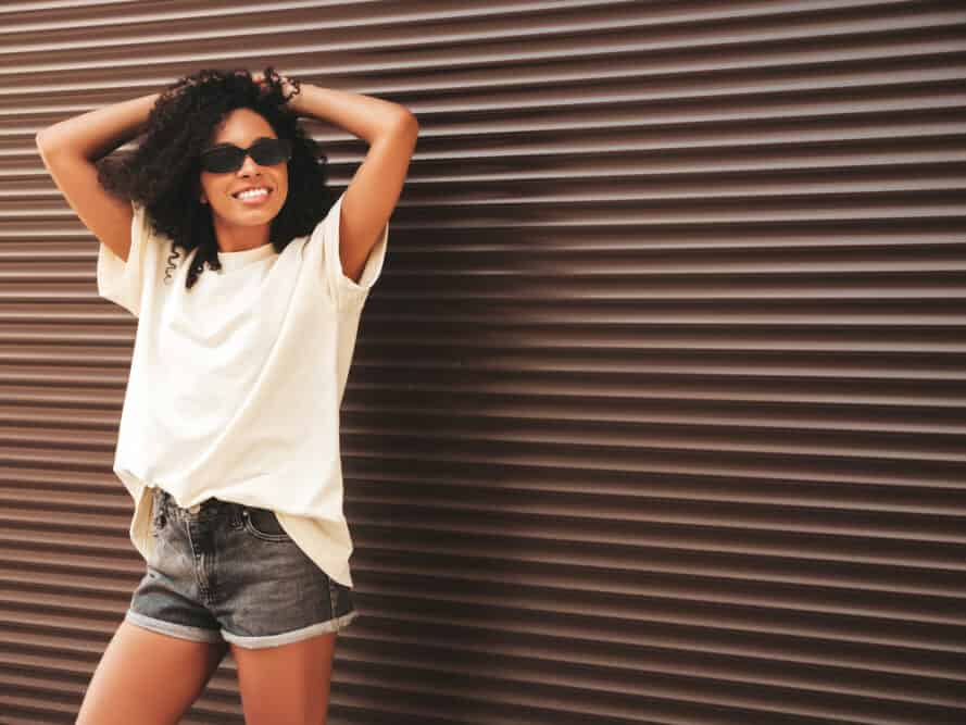 African American women with virgin hair wearing a white t-shirt, blue jean shorts, and loose curls.