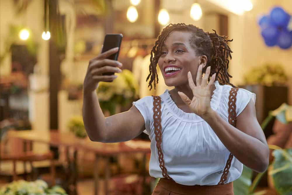 Black lady smiling while taking a photo on her cell phone.