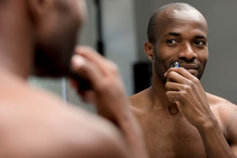 Black man with thick afro hair using cordless clippers to edge-up his mustache.