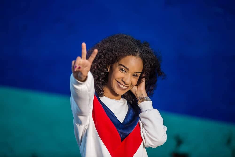 Cute black girl wearing a red, white, and blue sweatshirt with curly hair weave blended with her naturally curly hair.