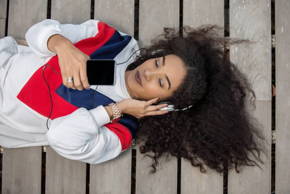 Black woman laying on the ground listening to headphones while wearing Virgin Indian hair extensions blended with her natural curl pattern.