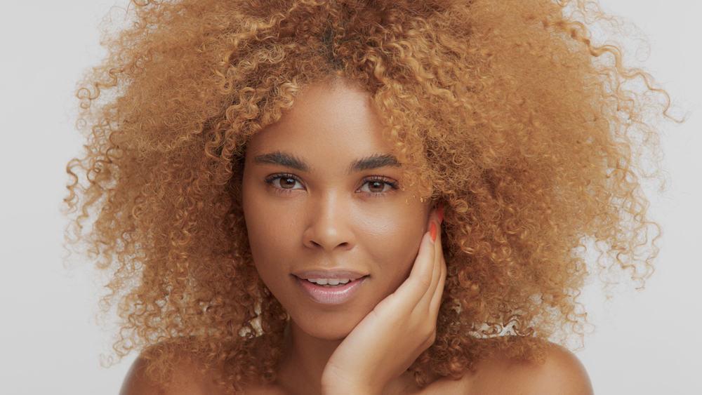 Pretty black girl with dark hair treated with a high volume developer for bleaching dark brown hair.