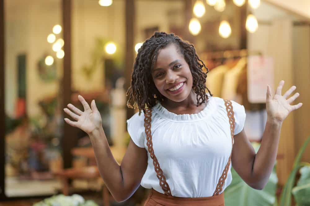 Black girl with wavy dreadlocks that look like braids, wearing a white shirt and brown dress.