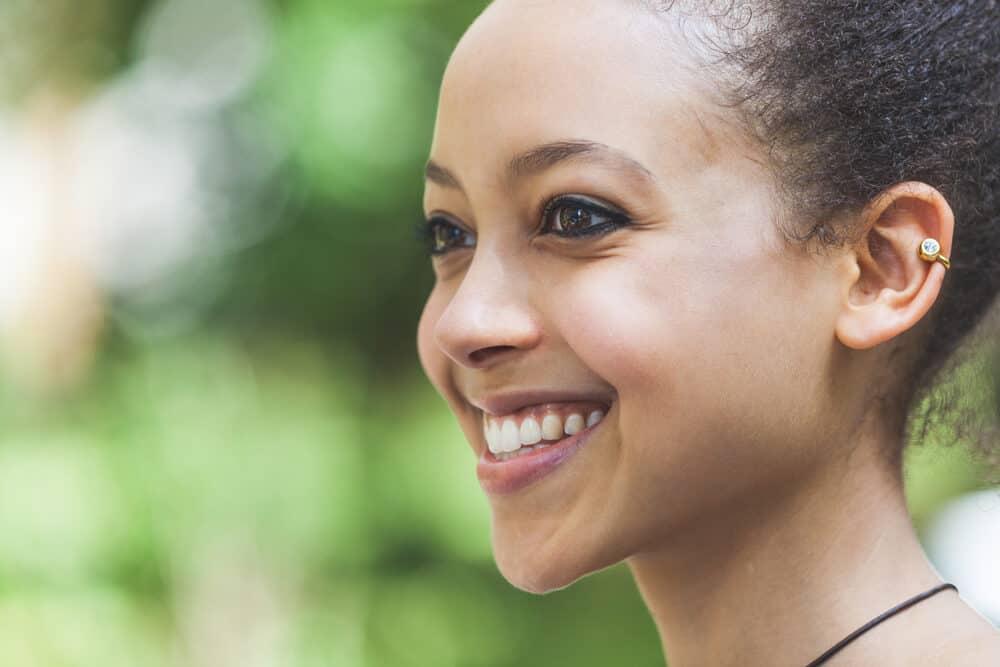 Cute black girl smiling and wondering if hair dye kills lice.