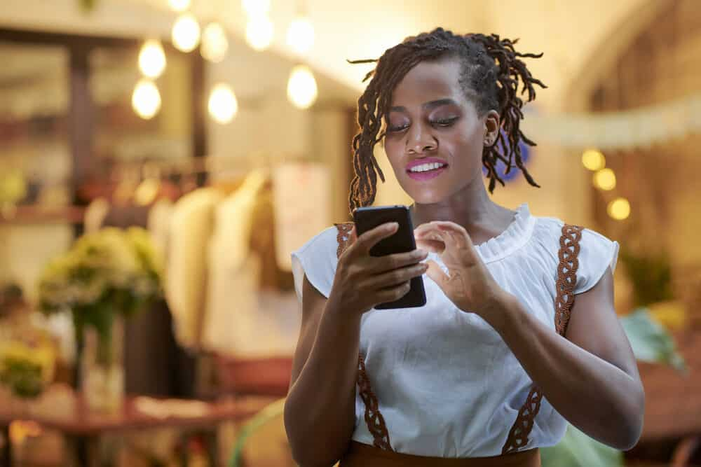 Cute woman with curly locks using her mobile phone at a department store.