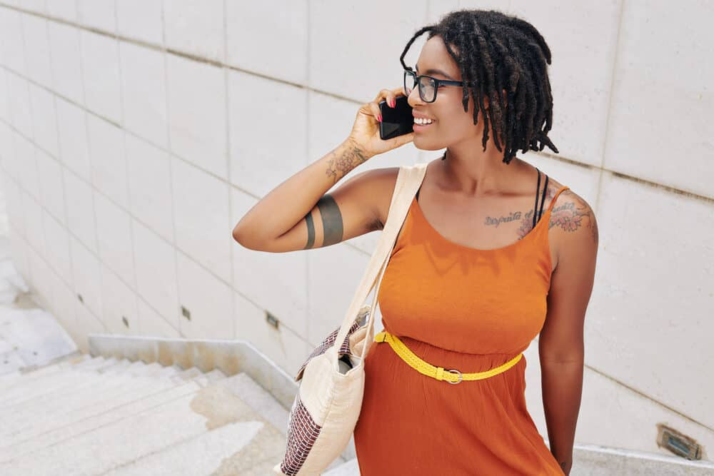An African American woman with a black hair color in an orange dress has a phone conversation, standing on the street.