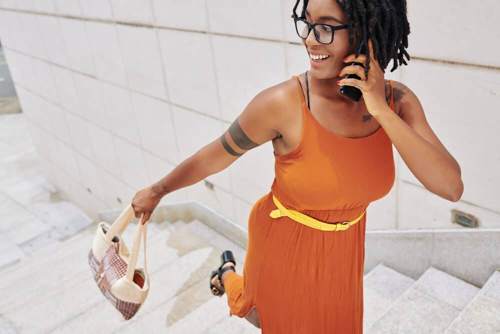 A young African woman in a bright orange dress talks on the phone while walking up the stairs.
