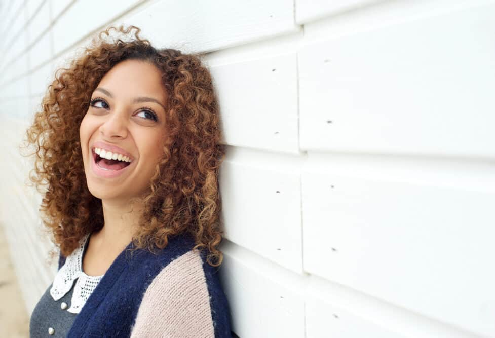 Lady laughing and enjoying life wearing curly short hair and partial highlights.