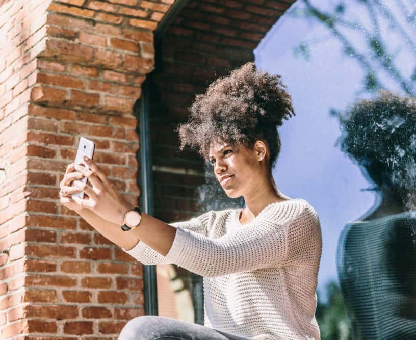 Beautiful young African American girl with a joyful expression, taking a selfie next to a large window and looking at herself in the reflection.