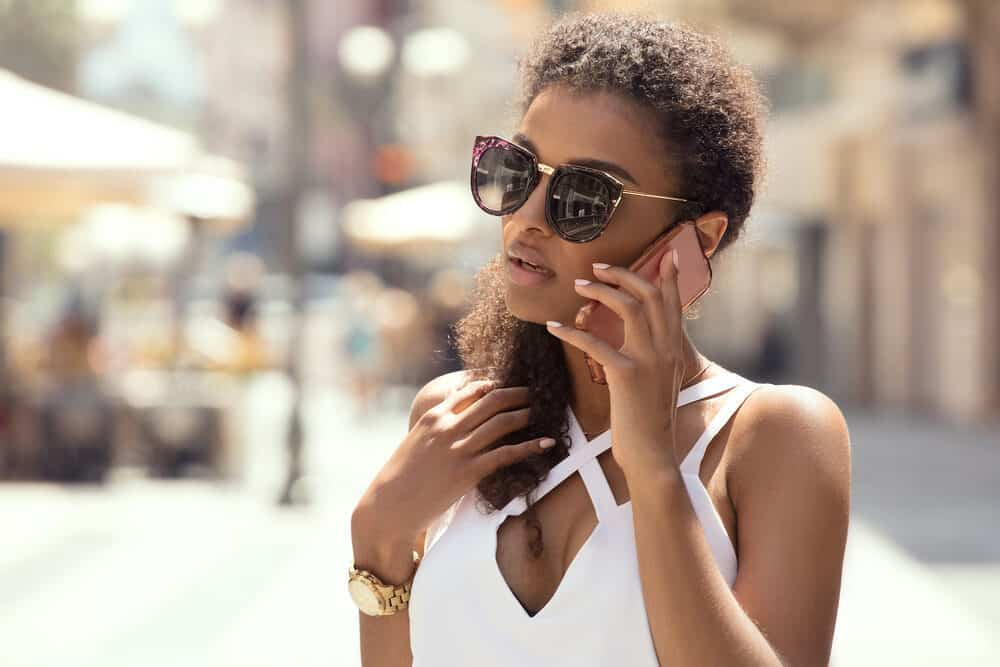 Black girl with curly hair wearing shades and using an Android mobile phone on a sunny day.