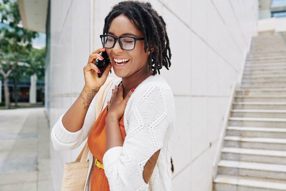 Pretty black lady with eyeglasses, peanut butter brown skin with her hair intricately styled in dreads, and wearing an orange dress, yellow belt, and beige purse.