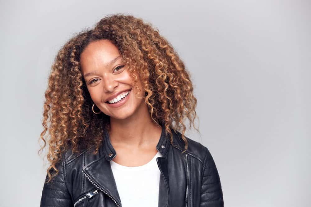 Black women with brown curly hair styled with light formula hairspray and hot rollers wearing a black leather jacket and a white t-shirt.