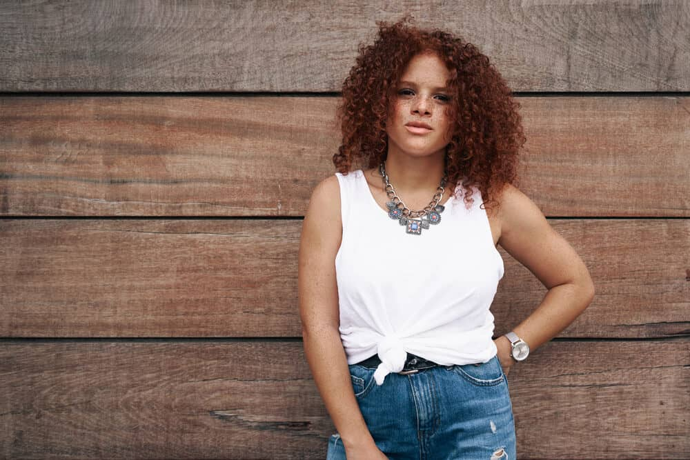 A woman in casual clothes is standing on the wooden background. She has curly red hair with orange undertones and freckles across her face.