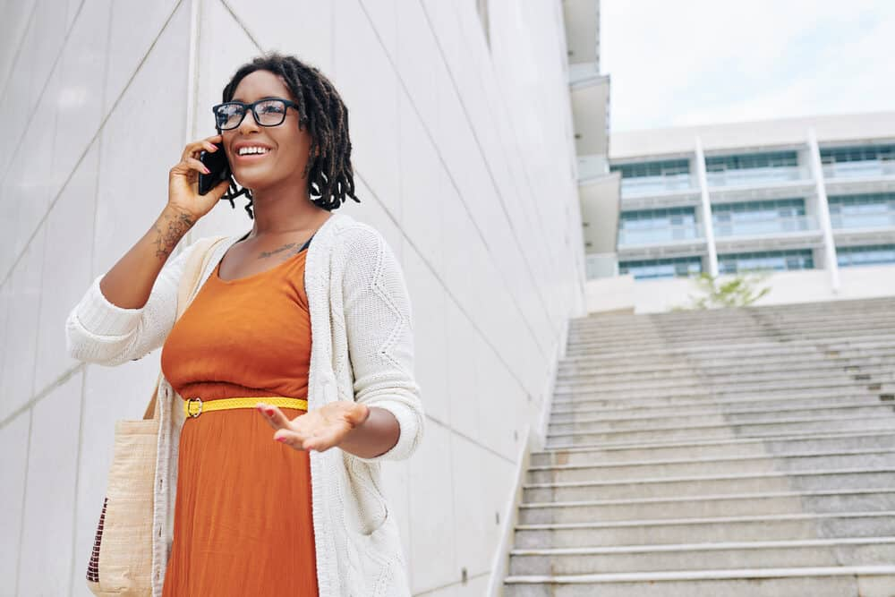 A woman talking on her phone in a city while wearing an orange dress and white sweater.