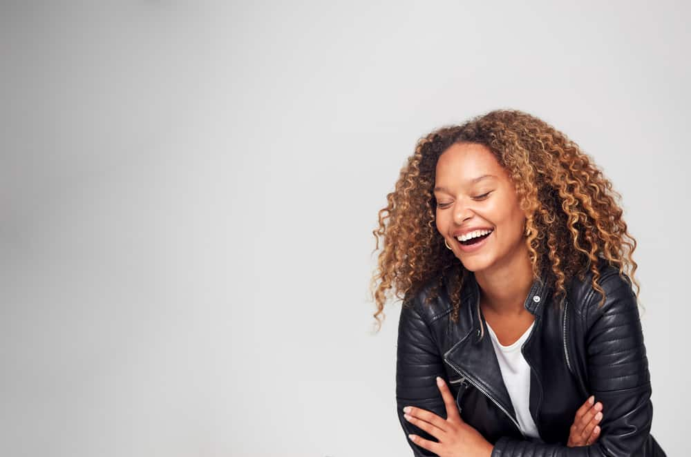 Women laughing with her eyes closed wearing a curly brown hairstyle.