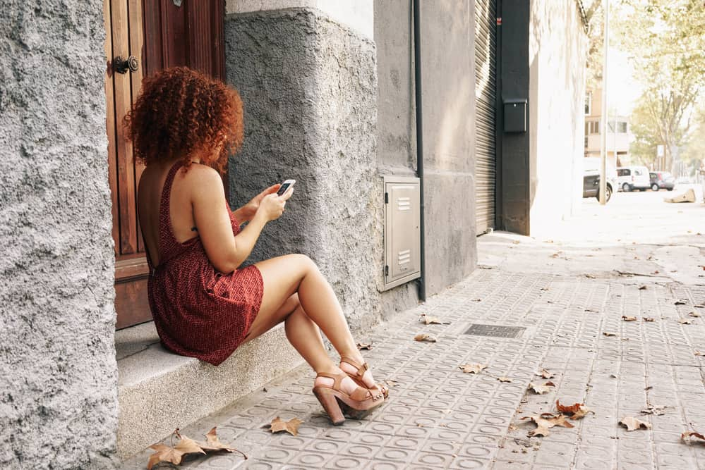 A woman with red pigments in her hair wearing a dress and sandals sits on the sidewalk beneath a tree, talking on her smartphone.