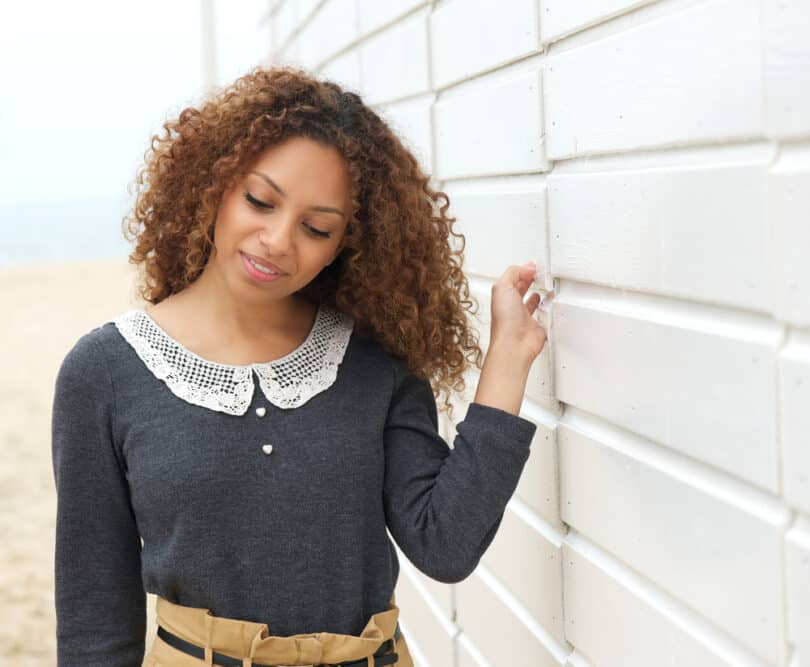 Cute black girl with dark hair with a partial balayage inspiration wearing a gray dress and brown pants.