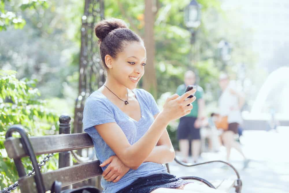 Black lady sitting on a park bench while using an iPhone 12 with naturally curly hair.