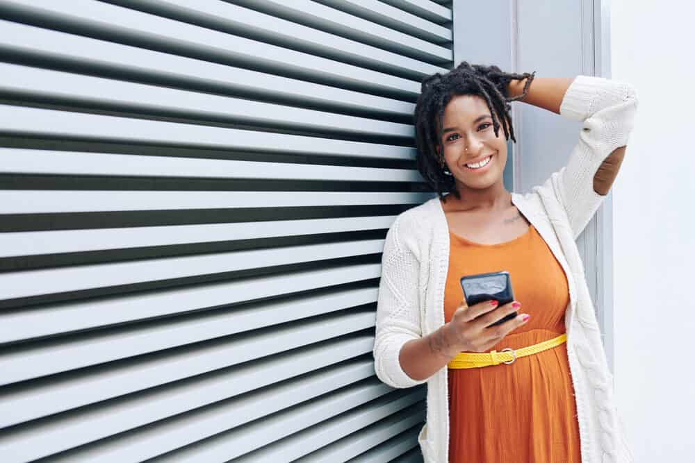 African woman on her dreadlock journey in an orange dress standing with a mobile phone and smiling at the camera against a striped wall outdoors.