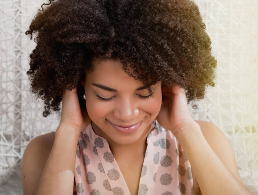 Light-skinned black girl plays with her hair giving obvious non-verbal cues about her mood.