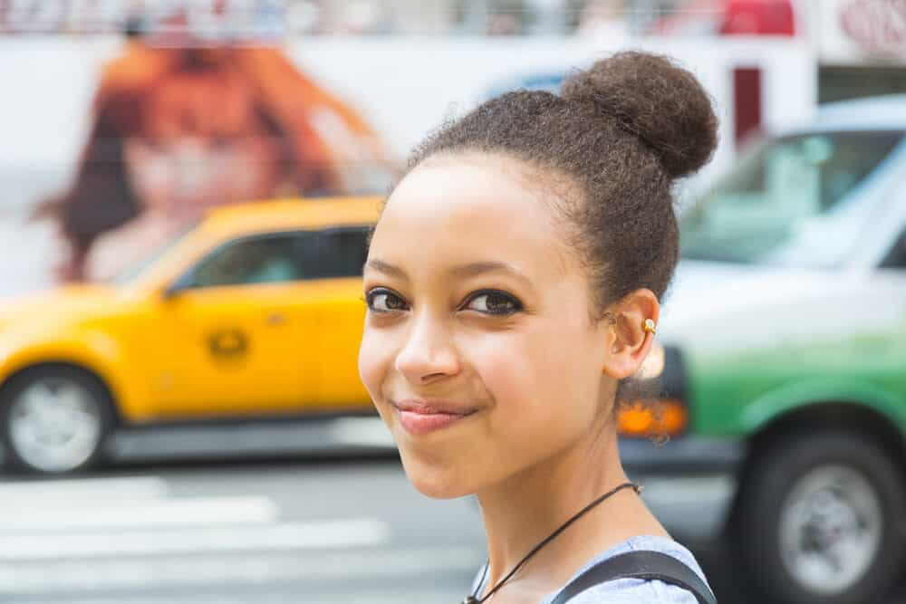 Black girl with brown colored hair, blue eye shadow, and a great smile.