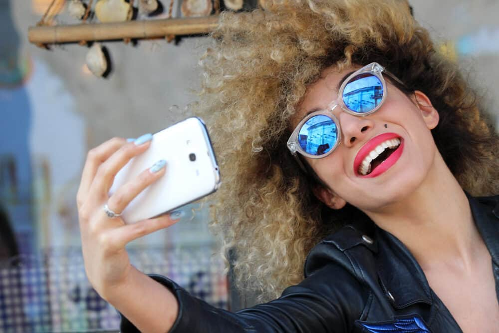 Mixed female smiling while taking a selfie wearing curly hair strands with brassy undertones.