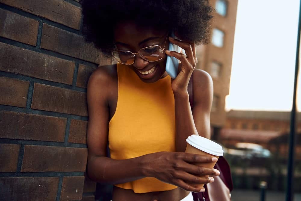 A smiling lady standing near a brick wall with a coffee while talking on her phone.
