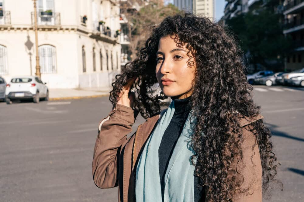 A charming Latina woman with curly hair treated with a water-soluble styling product