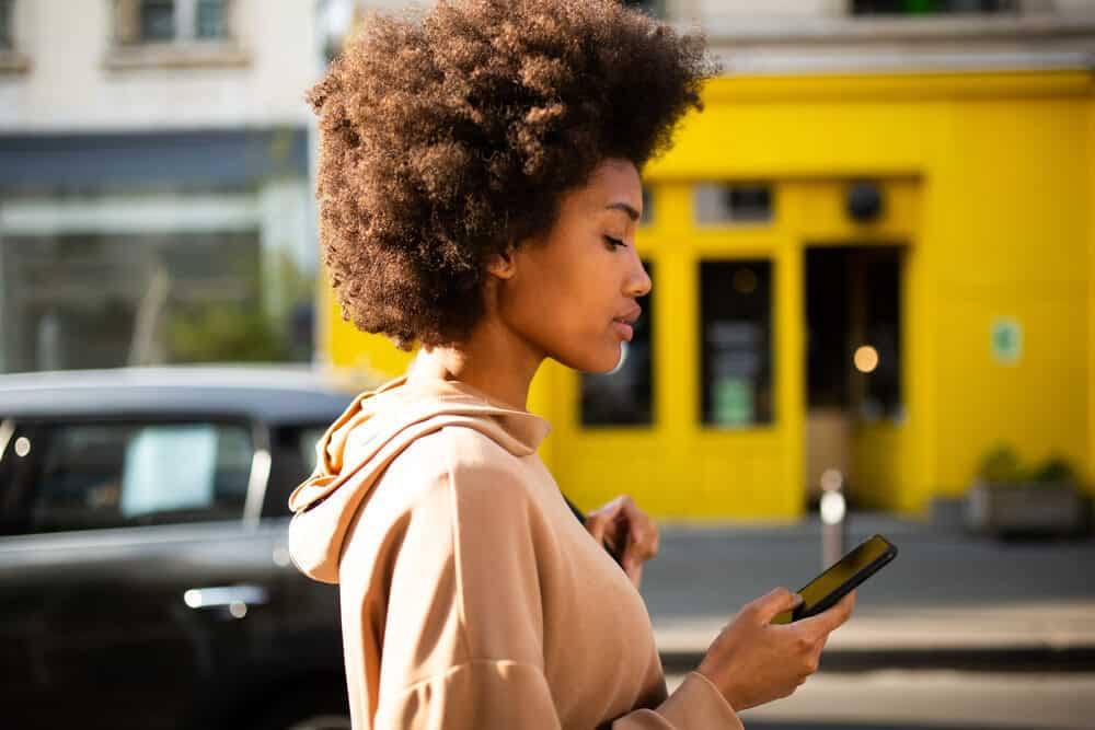 Lady with natural curls reading about her natural hair journey on the Curl Centric website.