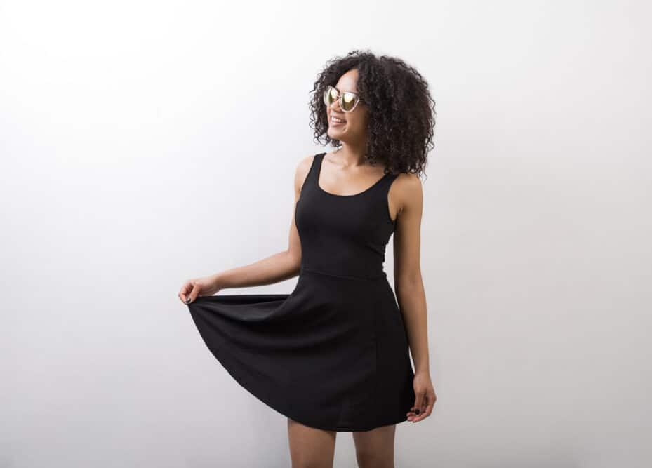 Lady wearing a black dress and sunglasses enjoying her curly hair journey with big curly waves