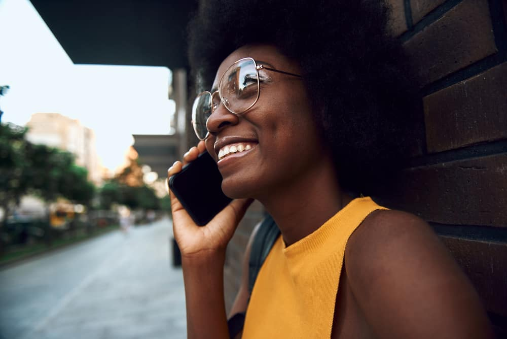 Cute black woman with naturally curly hair in glasses talking on the phone while leaning against a brick wall.